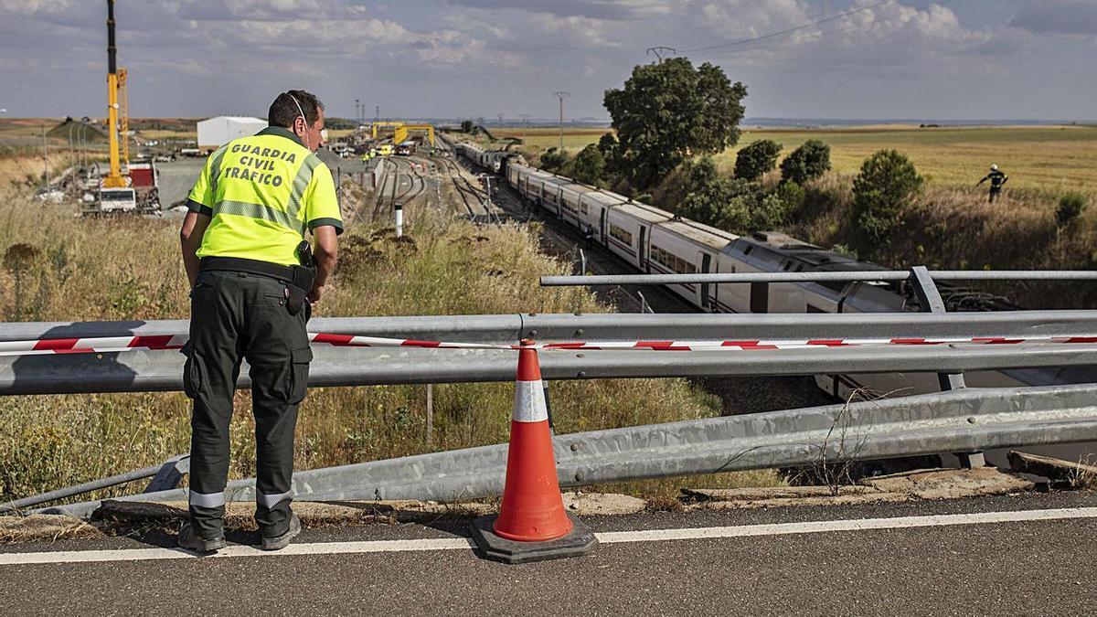Un agente de la Guardia Civil recoge pruebas en la zona del accidente.
