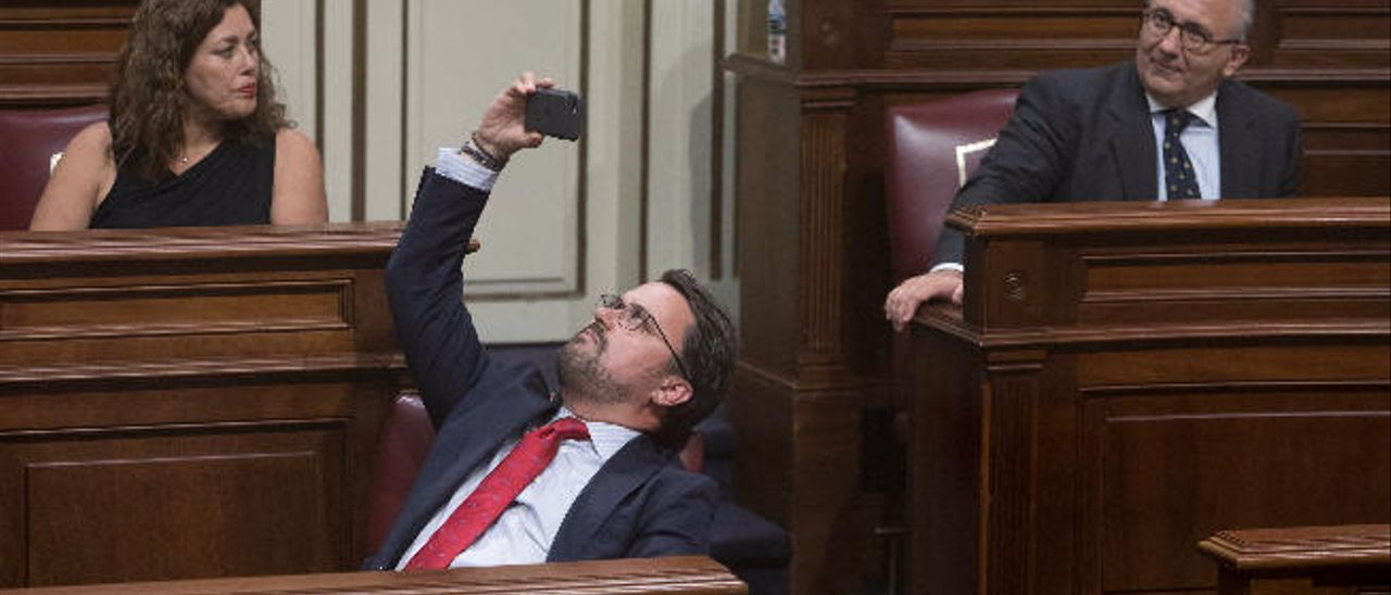 Asier Antona hace una foto con el móvil en su escaño del Parlamento.