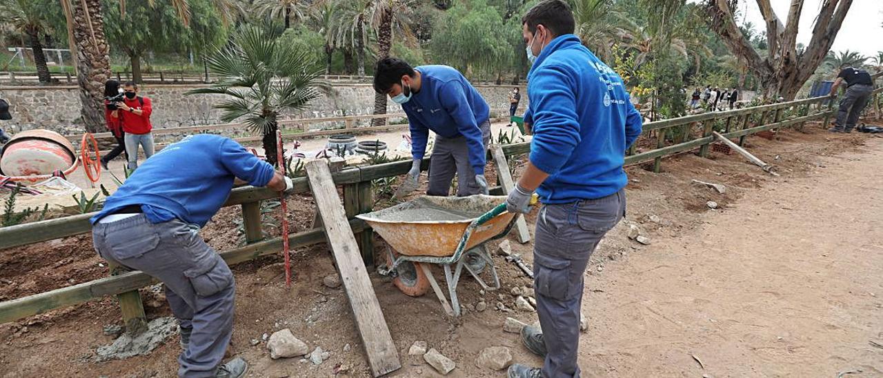 Alumnos del programa de empleo colocando ayer una valla en la ladera.  | ANTONIO AMORÓS
