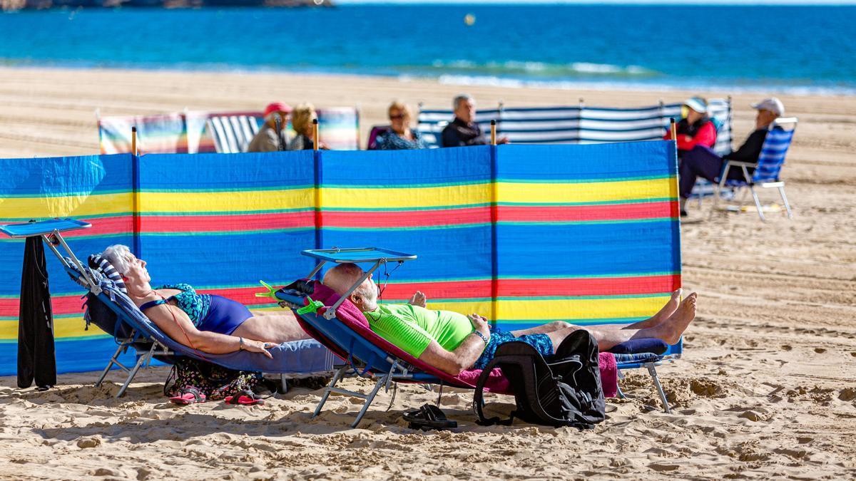 Turistas tomando el sol en la playa de Levante de Benidorm en febrero