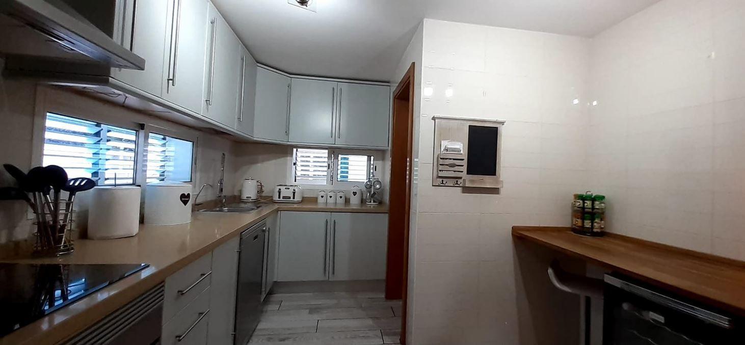 La cocina cuenta con nevera empotrada, lavavajillas y barra de desayuno.