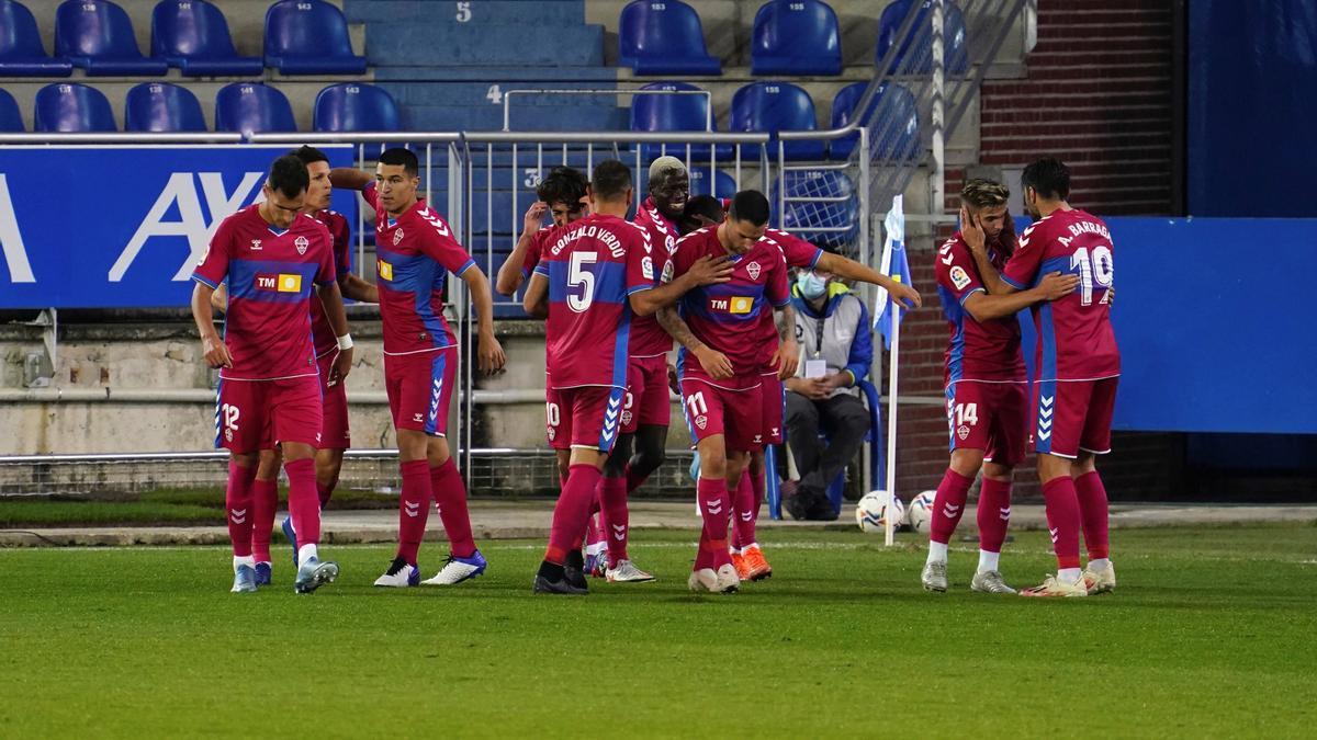 Los jugadores del Elche con la camiseta roja celebran uno de los goles frente al Alavés