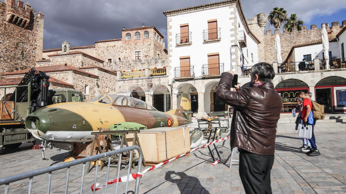 Un cacereño fotografía a uno de los aviones militares, durante su montaje este lunes en la plaza Mayor.