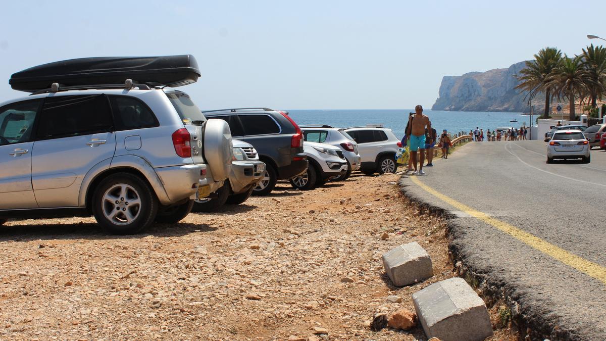 Banyistes i cotxes mal aparcats a la platja de les Rotes, en una imatge de fa dos estius