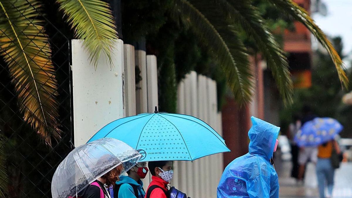 Tres xiquets van camí de l'escola durant l'inici d'este curs amb paraigües i mascaretes.  | F.CALABUIG