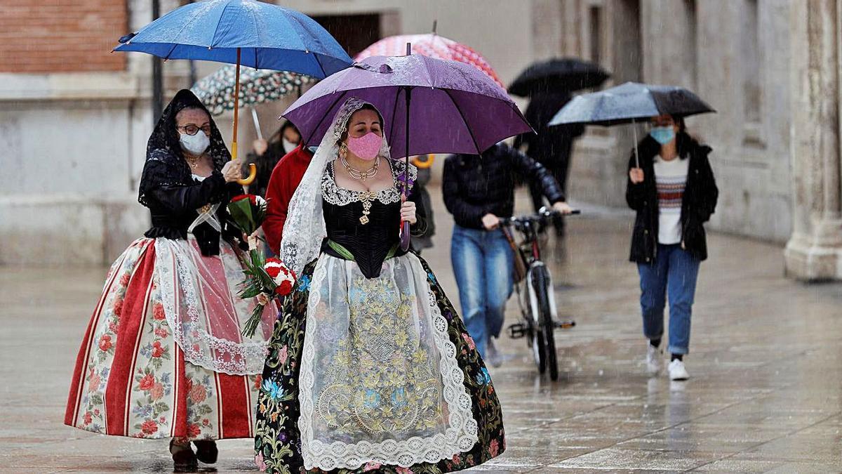 La ofrenda espontánea del 18 de marzo por la mañana estuvo marcada por la lluvia.  | BIEL ALIÑO / EFE