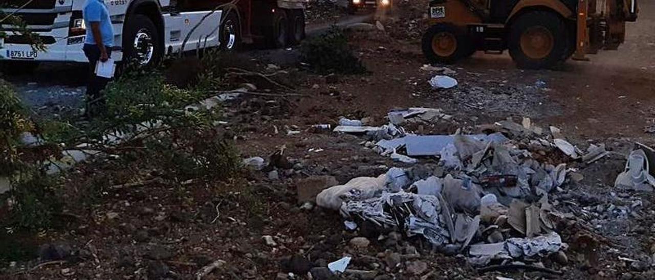 Un operario carga de escombros un camión con la retroexcavadora, ayer. | |
