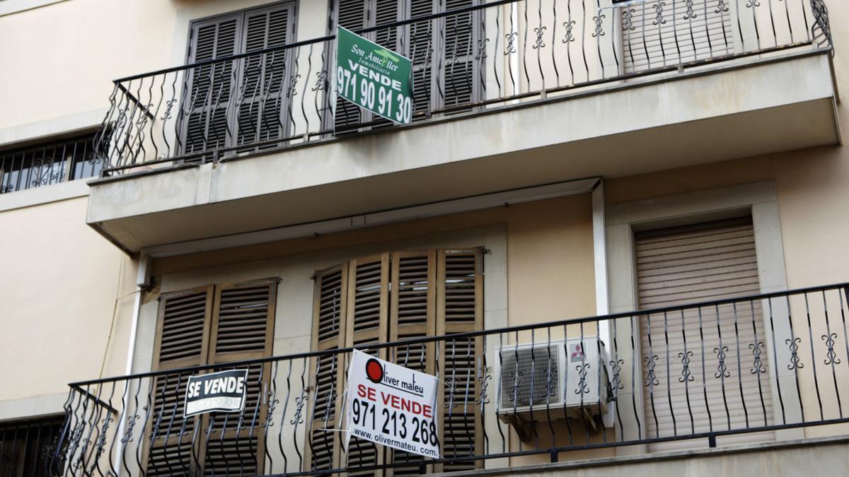 Varios carteles de venta colocados en los balcones de un bloque de viviendas.