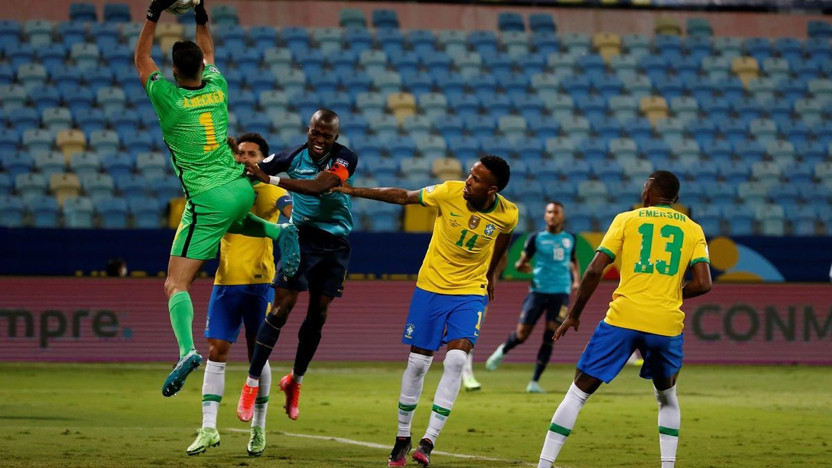 El guardameta brasileño Alisson atrapa la pelota ante la presión de un futbolista ecuatoriano.