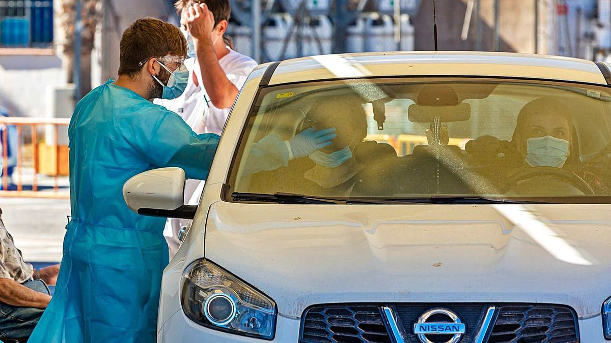 Patients in their vehicles undergo a sample collection for a PCR test.  |
