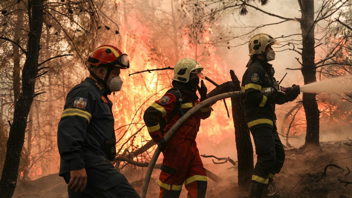 Tres bomberos trabajan para sofocar un fuego en la isla de Evia.