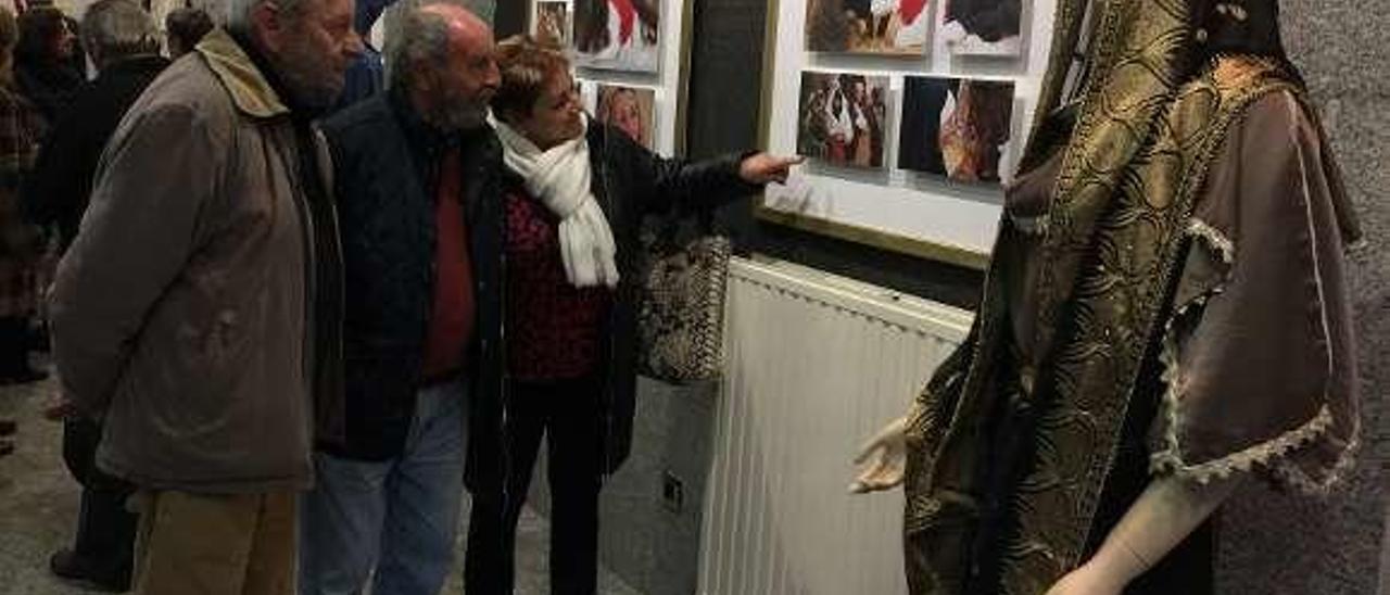 Asistentes a la inauguración de la exposición sobre el vía crucis viviente de Infiesto observan algunas de las fotografías de la muestra, ayer.