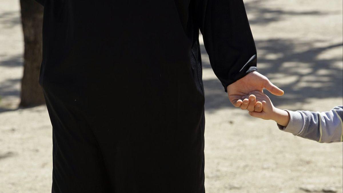 Un sacerdote lleva de la mano a un niño.