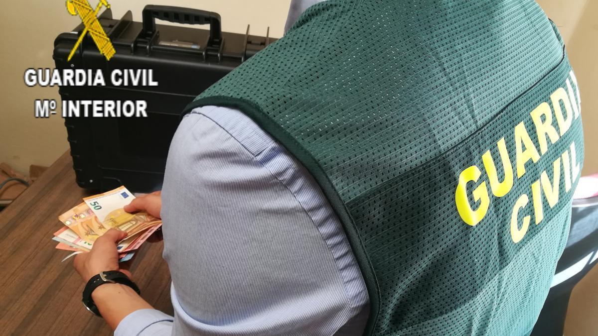 Un agente de la Guardia Civil cuenta dinero intervenido en la operación.