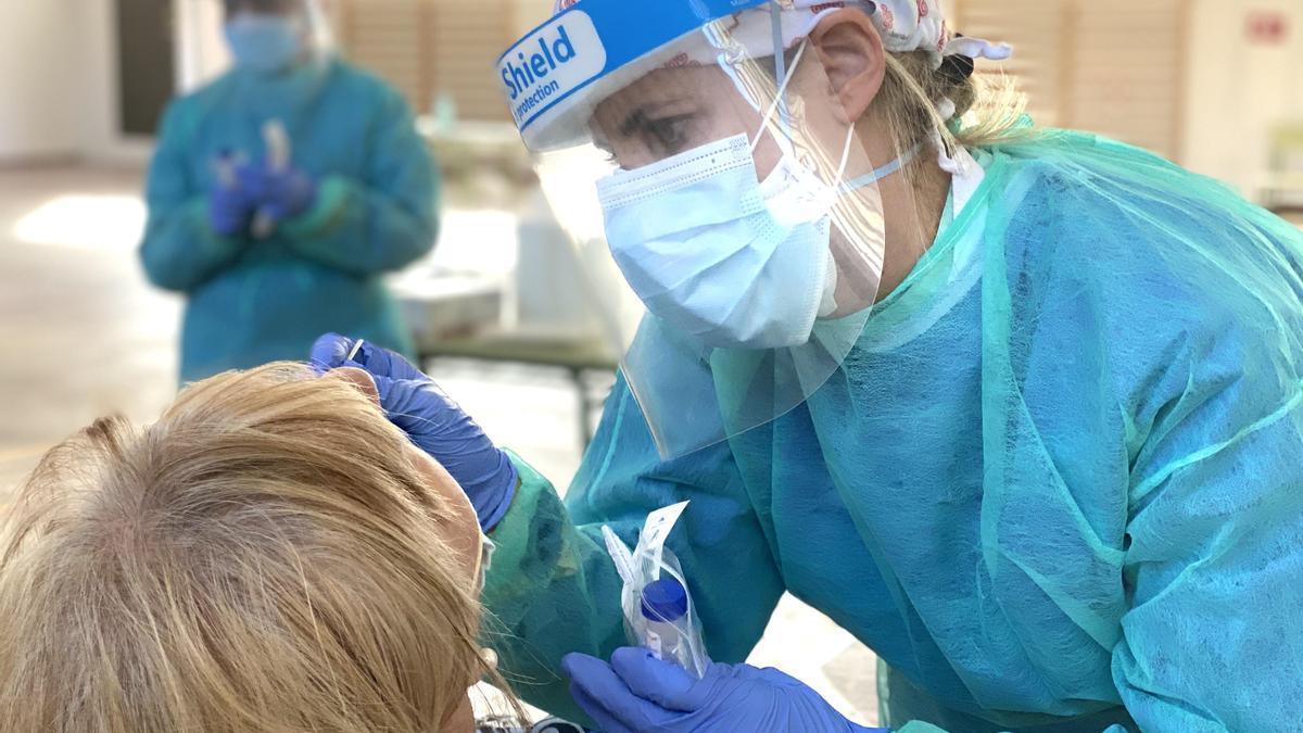 Una sanitaria realizando la prueba del PCR a una paciente.
