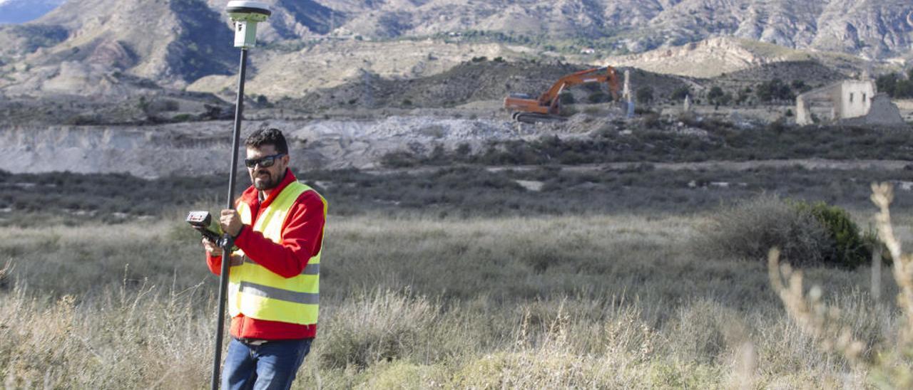 Un operario realizando ayer mediciones mientras una excavadora derriba una casa en ruinas en la parcela de la futura planta solar.