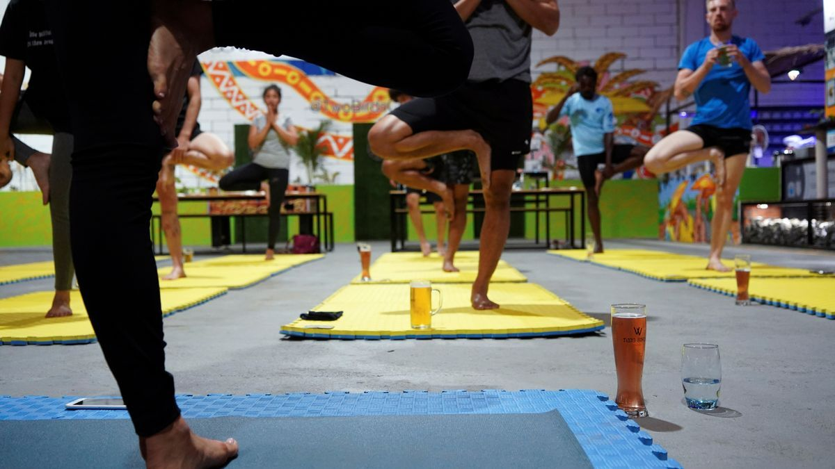 People participate in a beer yoga session, as the country eases COVID-19 restrictions, at a craft brewery in Phnom Penh