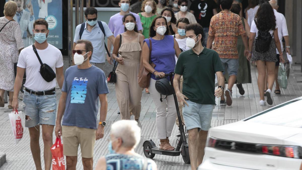 Varias personas pasean con mascarilla por la calle Colón.