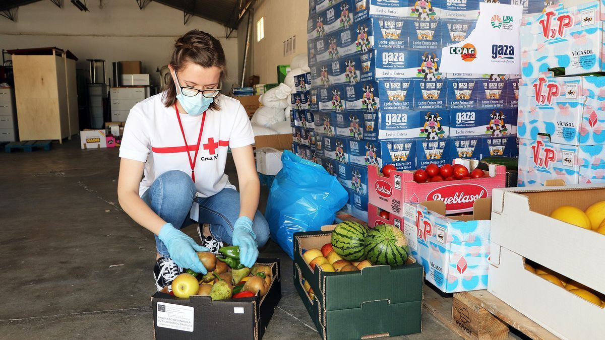 Una voluntaria de Cruz Roja distribuye alimentos.