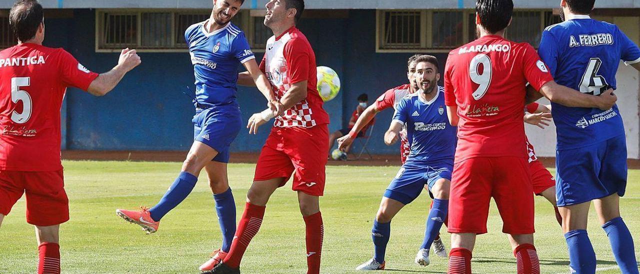En el centro, Font, de azul, y Jorge disputan un balón, con Pantiga a la izquierda y ante la mirada de varios jugadores del Cova y el Llanera.