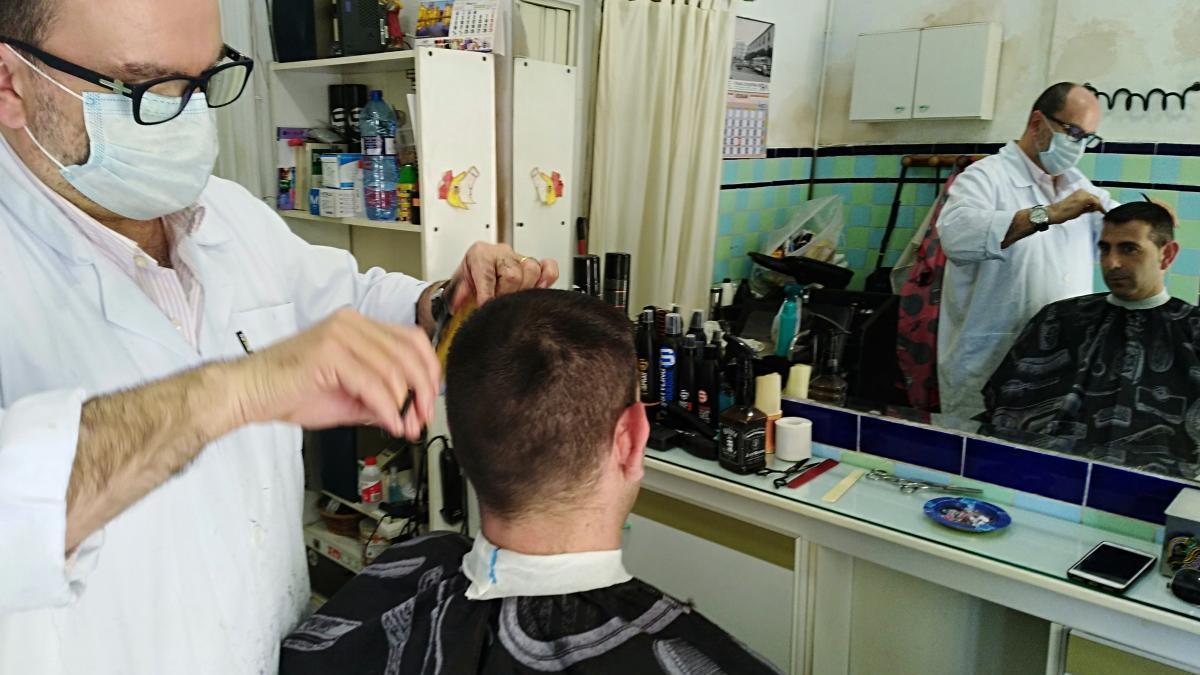 Camarena atiende a un cliente en su peluquería de Gandia.