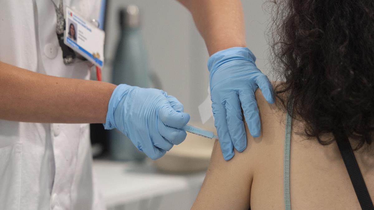Una joven recibe la primera dosis de la vacuna en el Hospital Zendal.