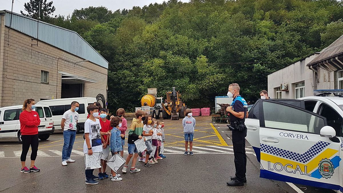 Un grupo de niños de la Escuela de Verano con agentes de la Policía Local de Corvera el pasado verano.