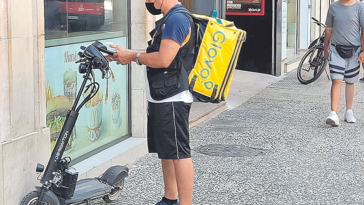 Un repartidor de Glovo espera a recoger un pedido, hoy, en el McDonald´s del Coso de Zaragoza.