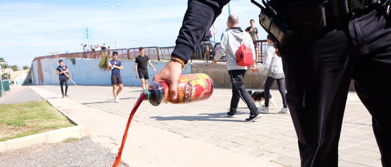 Un agente vaciando una botella, en la última celebración de la Santa Faz
