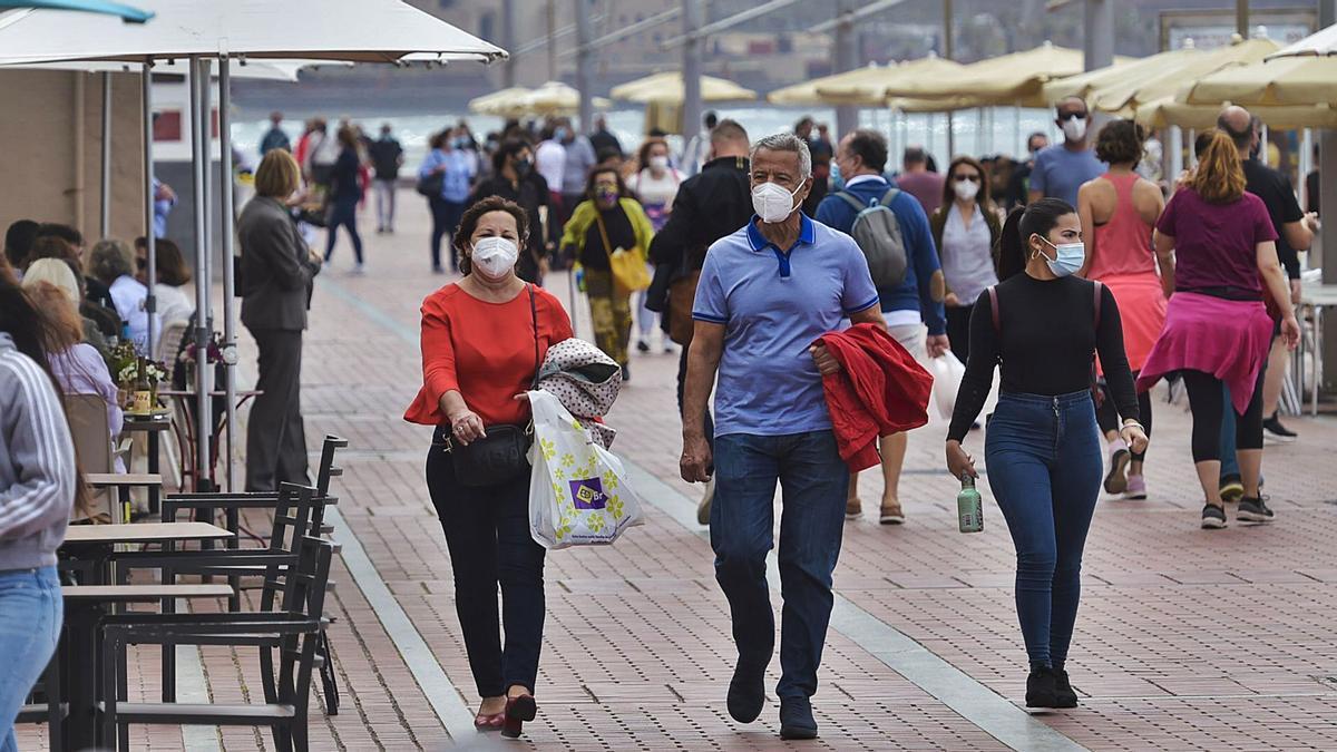 Gente con mascarillas por la calle.