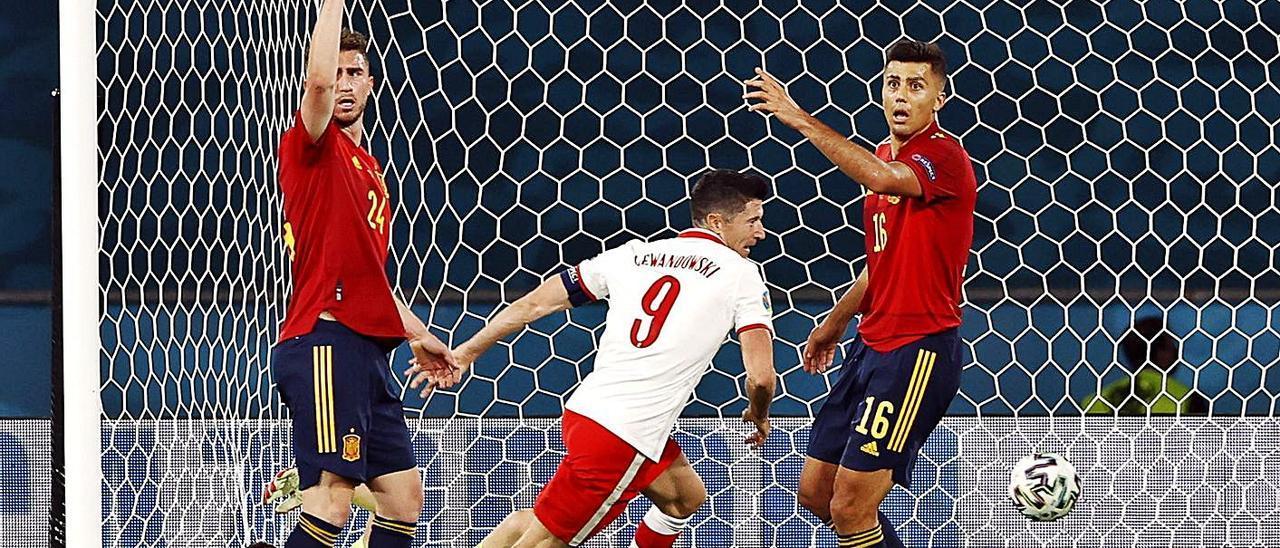 Lewandowski se dispone a celebrar su tanto con Laporte, Rodrigo y Unai Simón en el suelo. | Efe