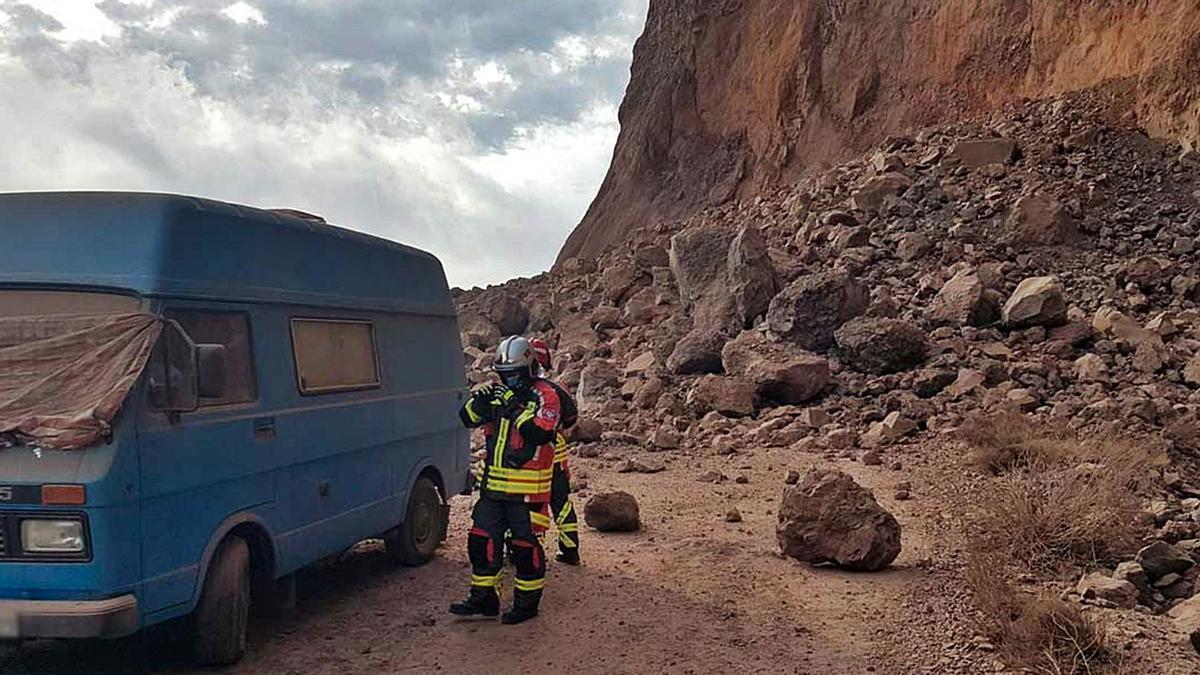 Bomberos junto a una de las caravanas aparcadas en la pista de Argaga y los restos del desprendimiento del sábado.     E.D.