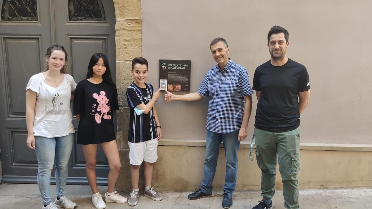 Una professora, dos alumnes, el regidor Calmet i un altre professor de la Fedac mostren el codi QR col·locat a la placa de la capella de Sant Ignasi Malalt