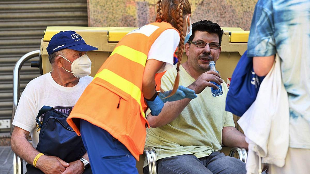 Óscar Fuentes, con la cara tiznada, recibe atención médica en la calle tras el incendio.