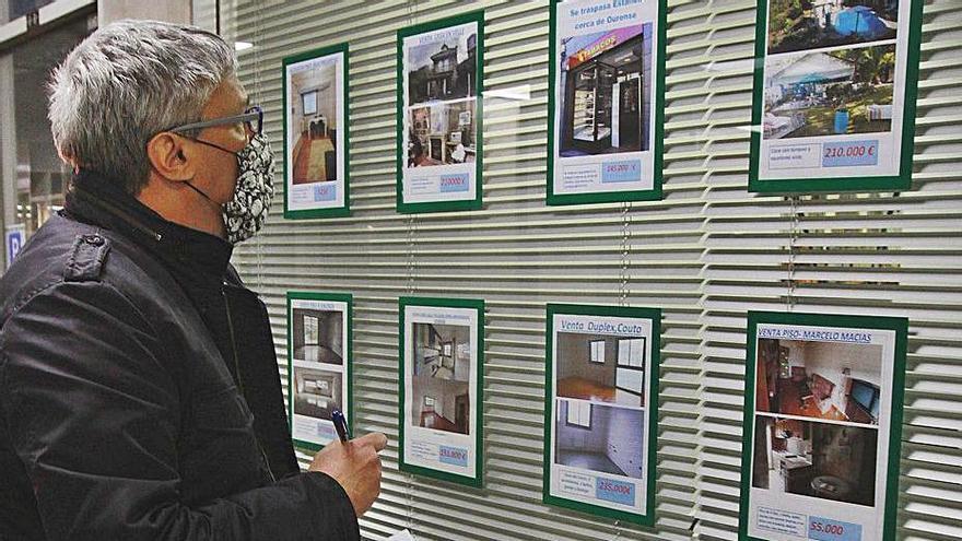 Un hombre consulta las ofertas de pisos en una inmobiliaria. |   // I. O.
