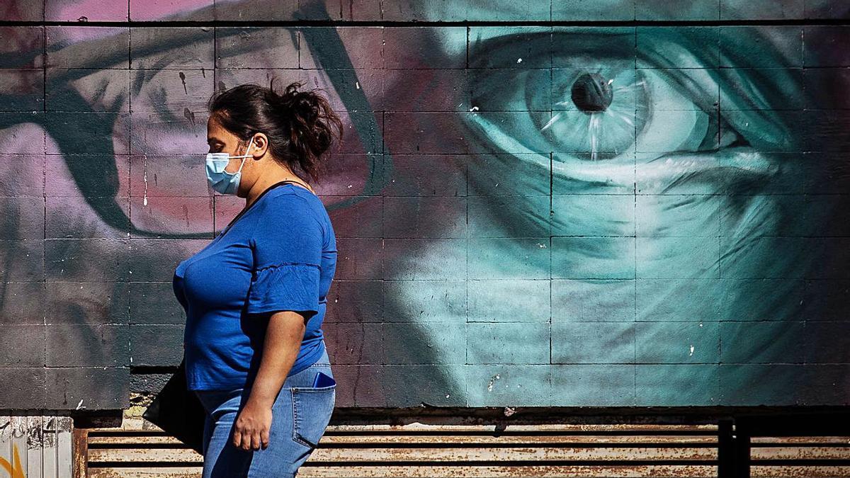 Una mujer pasea con mascarilla en la capital tinerfeña.