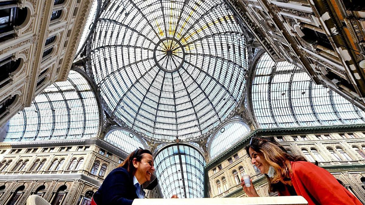 Unas mujeres toman café, ayer, en la galería comercial Umberto I de Nápoles, Italia.   | // CIRO FUSCO
