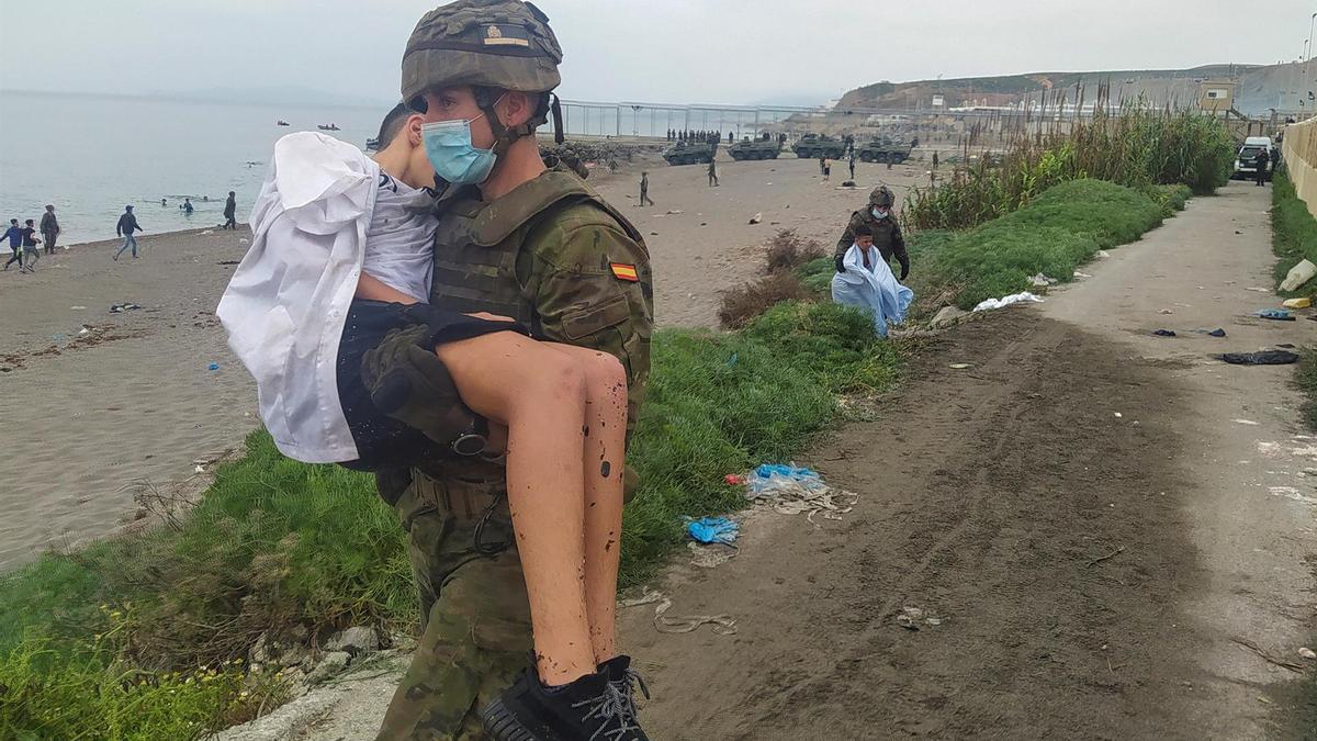 Un soldado español ayuda a un inmigrante en uno de los espigones fronterizos de Ceuta