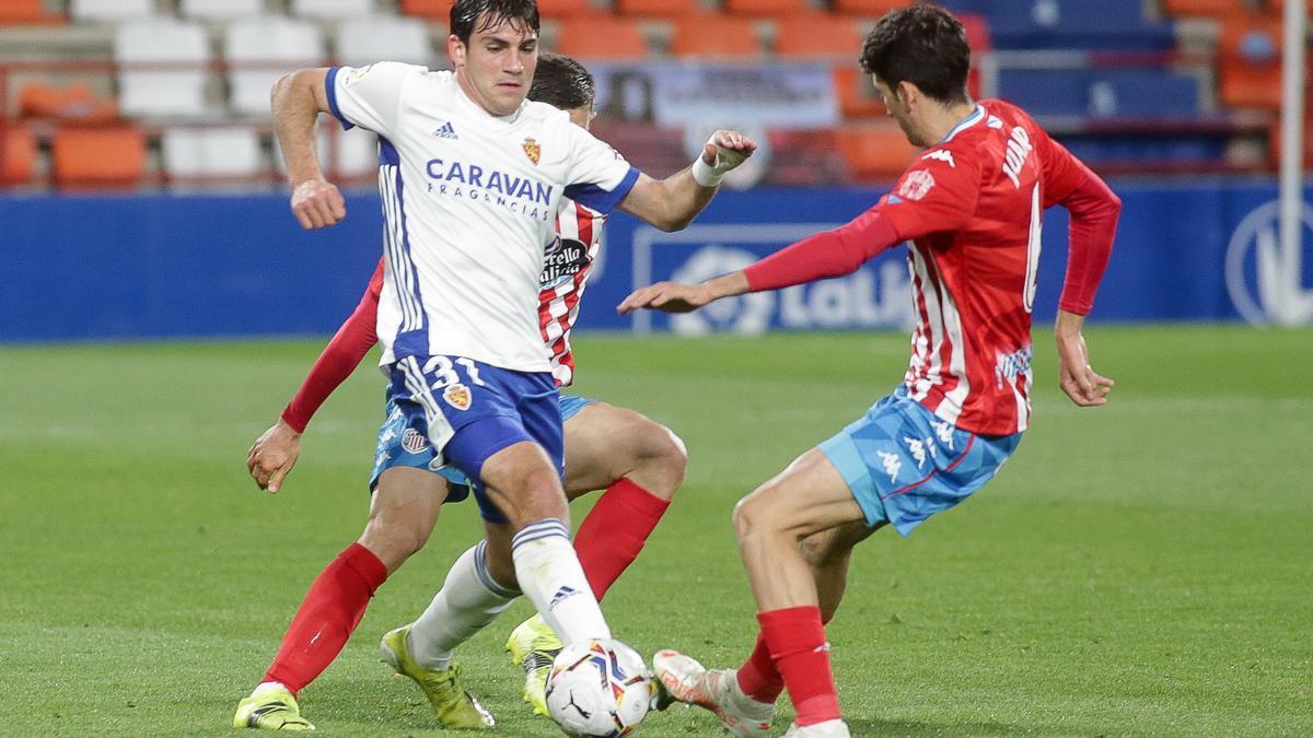 Azón trata de marcharse del asedio de dos jugadores del Lugo en el duelo del pasado viernes.