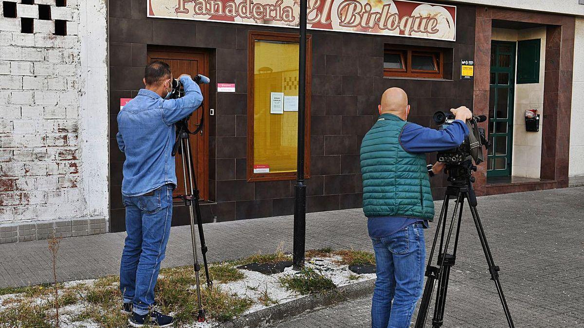 Dos periodistas frente a la panadería que regentaba la víctima.