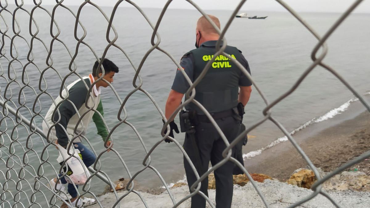 Un membre de la Guàrdia Civil ajuda un immigrant a la frontera entre el Marroc i Ceuta