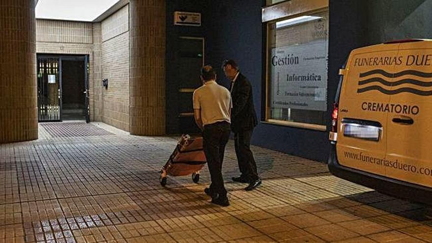Un trabajador de la funeraria accede al portal de la calle Donantes de Sangre antes de la salida del cadáver.