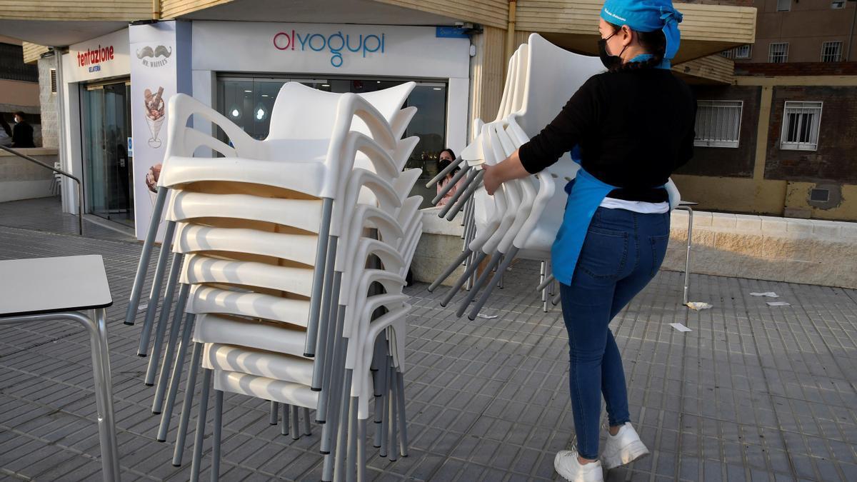 Una camarera recoge la terraza del establecimiento situado en el Paseo Marítimo de Almería