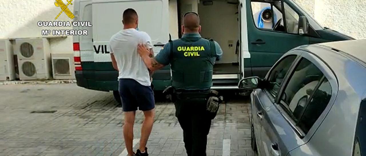 Un guardia civil conduce al furgón a uno de los detenidos en la operación-