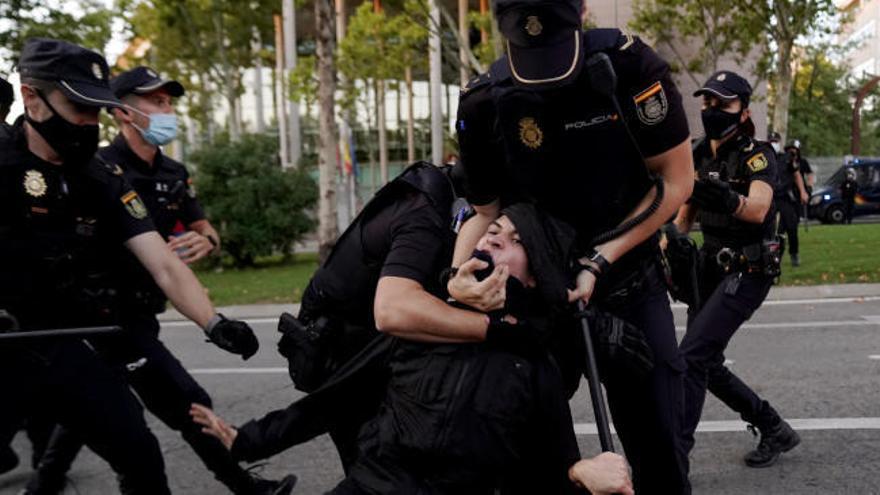 Enfrentamiento entre policía y manifestantes en una protesta contra los confinamientos en Madrid
