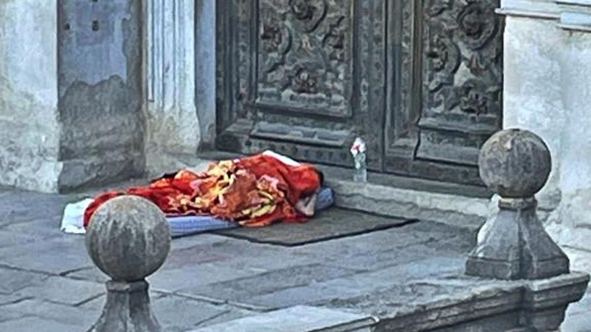 Una persona sens esostre dormint a la  portalada de la Catedral de Girona