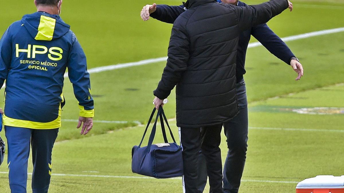José Mel Pérez abraza, el sábado en el Gran Canaria,  a un integrante del equipo médico del Rayo, club en el que pasó cuatro años. A la izquierda, Diosdado Bolaños.  | | ANDRÉS CRUZ