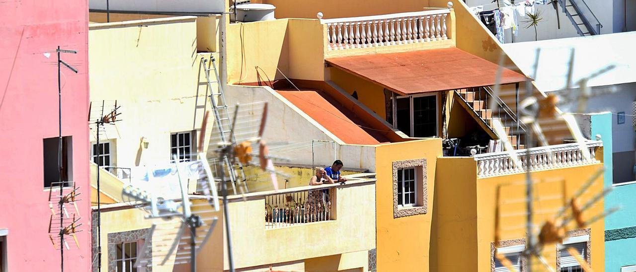 Vecinos del barrio de Pedro Hidalgo, en Las Palmas de Gran Canaria, se asoman a la azotea de sus viviendas. | | JUAN CARLOS CASTRO