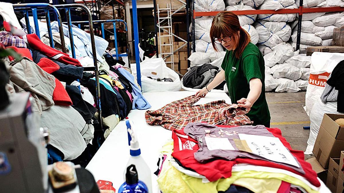 Arriba una responsable de Humana clasifica ropa. En detalle, una mujer introduce una bolsa en un contenedor de la Fundación en la comarca.