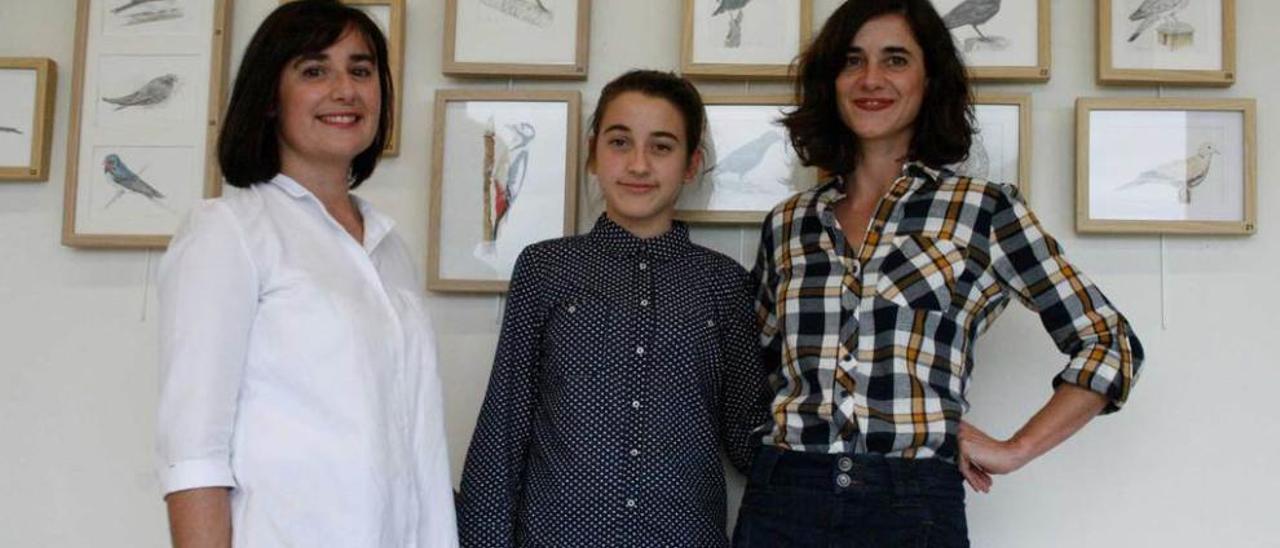 Isabel González, Olaya Ramiro y Rosa González, delante de su exposición de aves, en la biblioteca de Lugo.